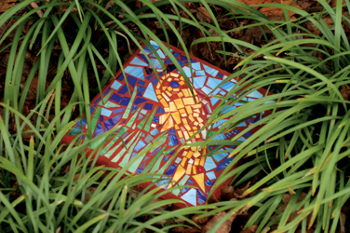 stepping stone with colored glass top in long grass