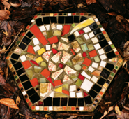 stepping stone covered with broken colored pottery laying in wet leaves