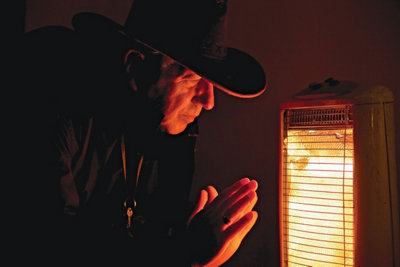 man leaning close with his hands up to a heater