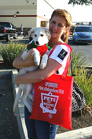 a woman carrying a newly adopted dog with a TSC bag containing pet adoption supplies