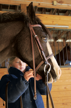 a girl checking on her horse's bridle