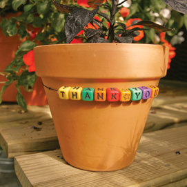 a pot with alphabet beads on an elastic string around it