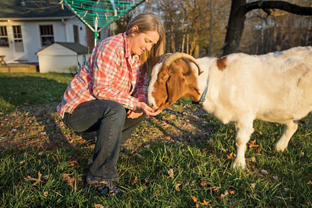 Betsy crouched down with a goat eating out of her hand