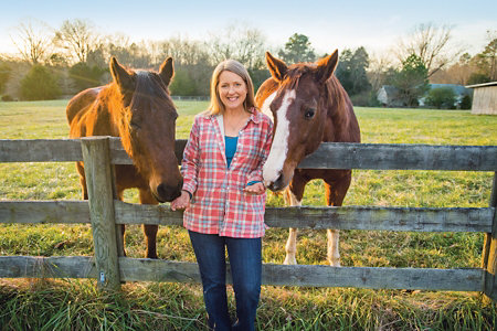 Betsy standing in front of a fence with two horses nuzzling her hands from behind the fence