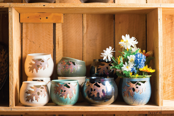 several short bowls with their leaf motif, flowers in the one on the far right