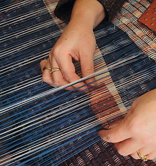 Karen's hands weaving weft (widthwise) fabric through the woof (lengthwise) fabric