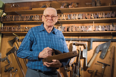 John in his tool shop with all the tools on shelves and hung on the walls