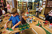 children playing with wooden trains on display