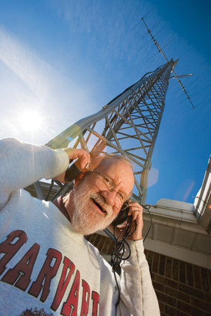 Don Neagle with his headphones on and the radio tower behind him