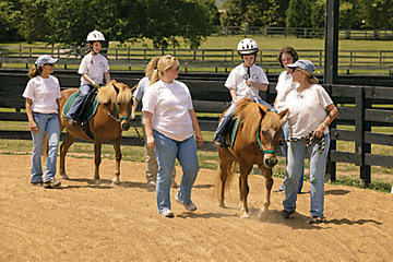 special needs children riding their horses with adult help