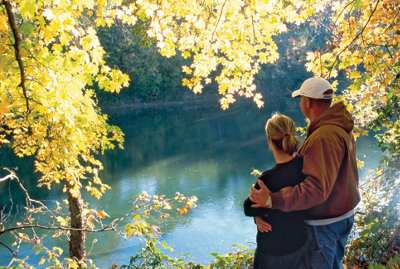 a couple overlooking a wooded river