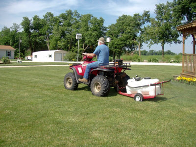 man using his riding mower to spread herbicide