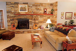 the living room with distinctive rock fireplace wall and a couple of guitars
