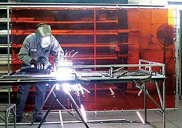 Man using a welder wearing a welding helmet.