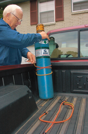 man securing a gas cylinder in an upright position in his pickup truck bed