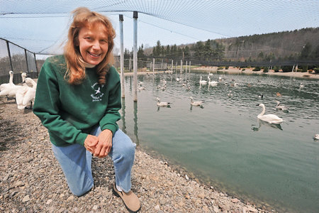 Rosemary kneeling in front of one of the sanctuary ponds with birds behind her and netting above her