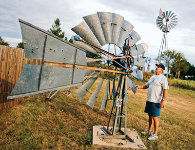 Chuck standing next to a windmill attached to a concrete base on the ground
