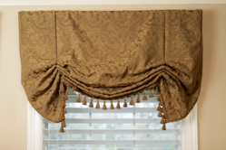 tablecloths with embellishments hanging on a window