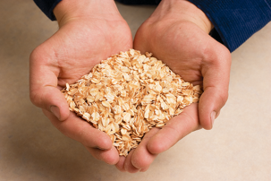 two hands cupped together filled with oats